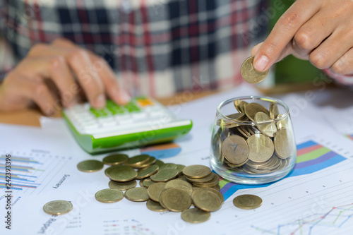 Photo Woman hand putting coinIn the glass jar