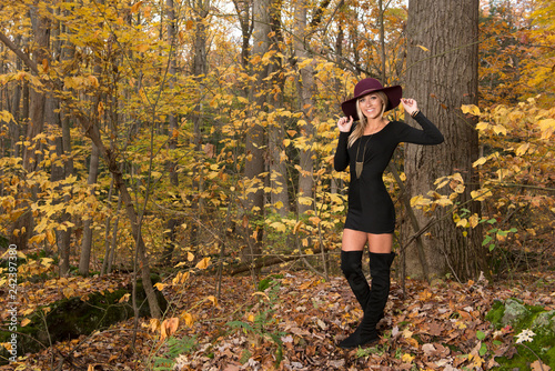 Fototapeta Sexy young blonde woman in stunning black dress and over the knee boots wears a