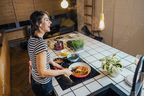 Poster Cuisine Young woman tasting a healthy meal in home kitchen.Making dinner on kitchen island standing by induction hob.Preparing fresh vegetables,enjoying spice aromas.Eating in.Passion for cooking.Keto diet