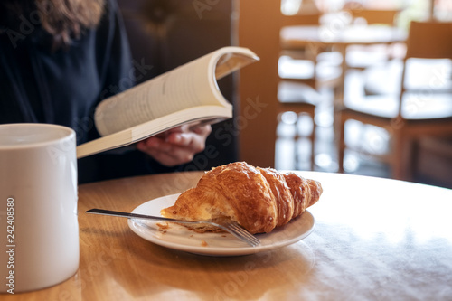 Foto Closeup image of a woman holding and reading a book with a piece of croissant in