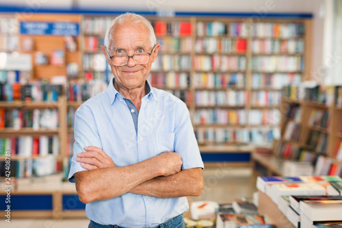 Photographie  Intelligent older man standing in library on background