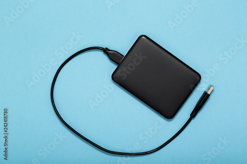 Fototapeta Black external hard disk with USB cable on blue background. Top view. obraz