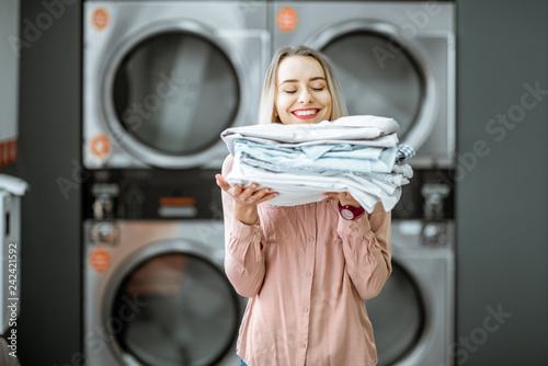 Photo Young woman enjoying clean ironed clothes in the self serviced laundry with drye