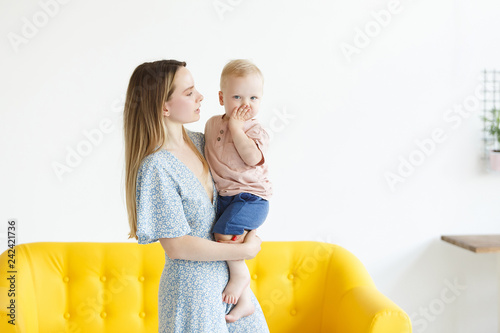 Fotografie, Obraz  Adorable young blonde mother in a beautiful dress holding her little cute son in a cozy homely atmosphere with a modern interior