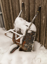 Wheelbarrow At A Construction Site In The Snow In Winter