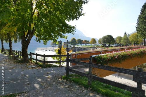 Keuken foto achterwand Molveno village walk along lakeside with a wooden bridge in the background