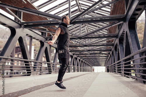 Fotografie, Obraz  Slim young male sportsmen jumping rope on the bridge