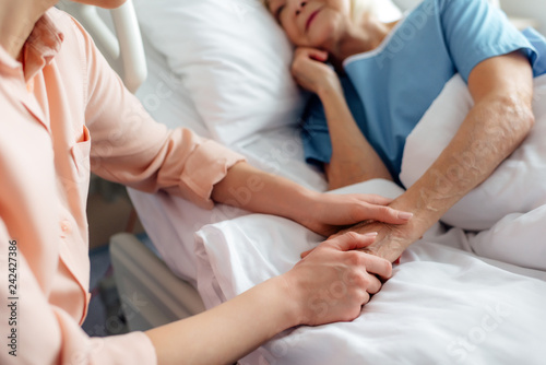 Fotografie, Obraz  cropped view of daughter sitting near senior mother in bed and holding hands in