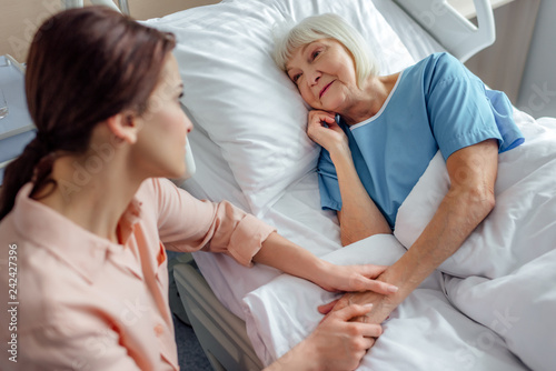 Leinwand Poster daughter sitting near senior mother in bed and holding hands in hospital