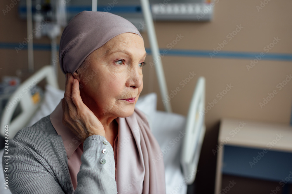 Fototapeta upset senior woman with cancer sitting on bed in hospital