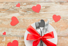 Valentines Day, Table Setting And Festive Dinner Concept - Plate With Spoon, Knife And Fork Tied With Red Ribbon On Wooden Background Decorated By Paper Hearts