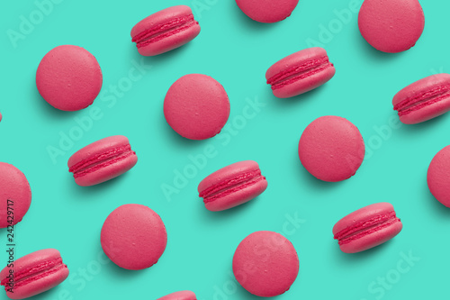 Poster Macarons Macaroons on colored background, a pattern of colorful french cookies macarons. Beige, brown french cookies macarons on red background. Gift for Valentine's Day