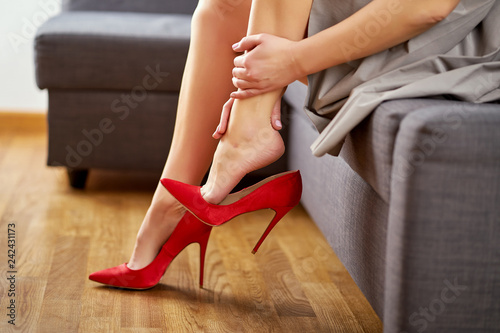 Fotografia  Business Woman taking off sexy red high heels shoes after work and massages painful feet at home on gray couch