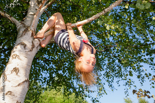 Photo  Happy girl hanging from a tree in a summer park