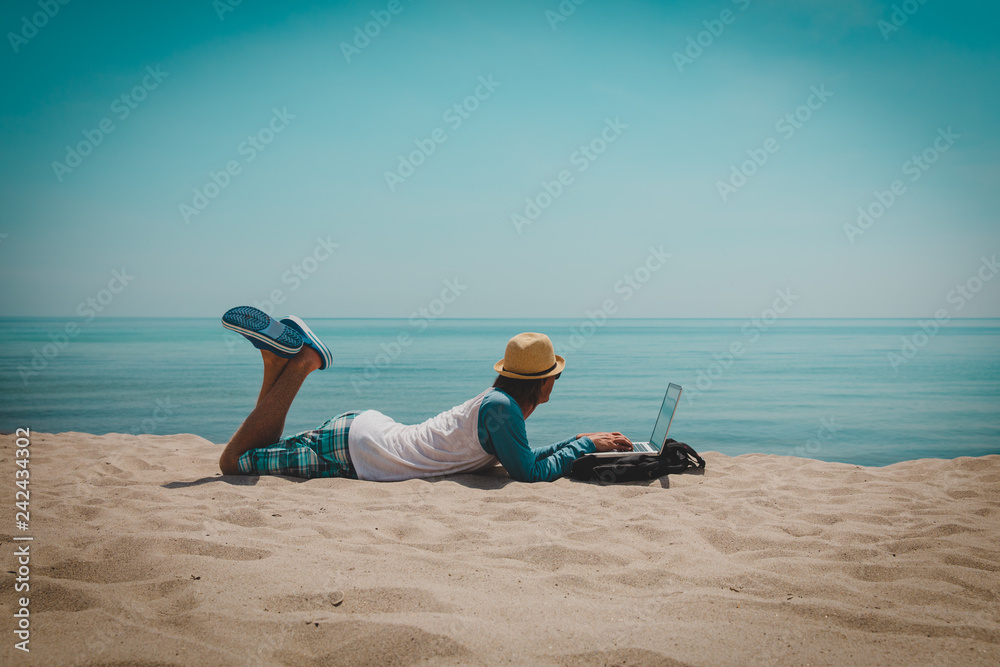 Fototapeta young man working on laptop at beach