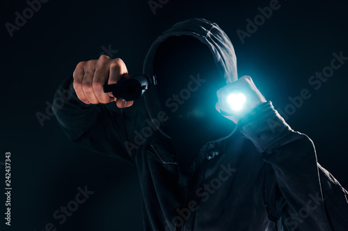 Fotografía  Armed robbery, criminal with gun and torchlight attacking in dark