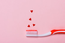 Toothbrushes And Shape Of Red Hearts On Pink Background. Dental And Healthcare Concept.