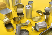 Tin Cans Isolated On Yellow Ba...