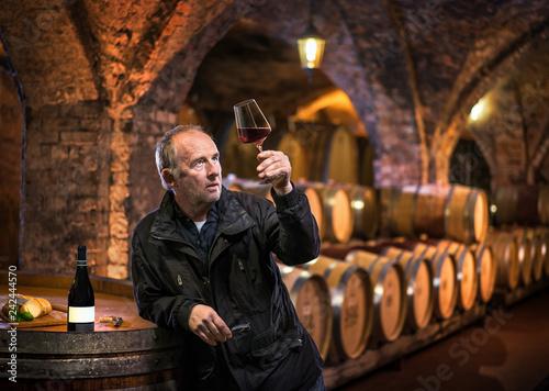 Fotografía  Mann begutachtet Rotwein - Weinprobe im Gewölbekeller