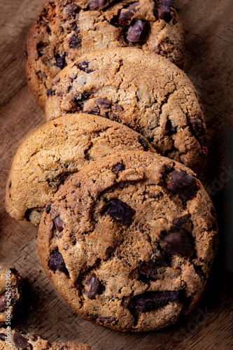 Freshly baked cookies with chocolate pieces on wooden background. Macro image