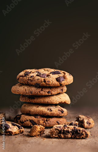 Stacked freshly baked cookies with chocolate pieces on wooden background, coppyspace. Macro image
