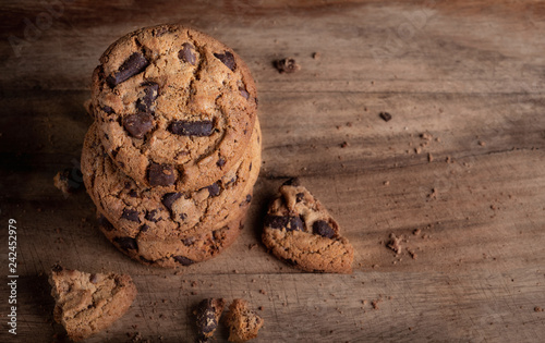 Dark Chocolate chip cookies with chocolate pieces on wooden background. Copyspace. Macro image
