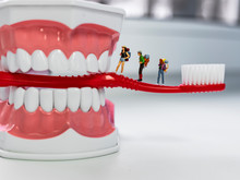 Miniature Figures. Tourists Stand On A Toothbrush And Look At The Jaw As A Landmark. The Toothbrush Sticks Out Of A Huge Jaw With Snow-white Teeth.  The Background For The Dental Clinic.