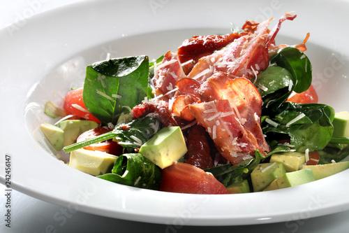 Fototapeta  Sałatka z pieczonym bekonem. Apetyczna sałatka z zielona sałatą, awokado, pomidorem i chipsem smażonego bekonu. obraz