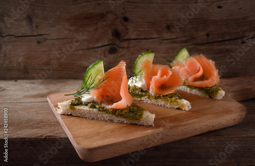 Deurstickers Buffet, Bar canapes in a row with smoked salmon, cucumber, pesto, cream and dill garnish on a rustic wooden board, copy space, close up