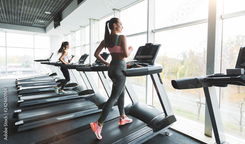 Woman running on treadmill at panoramic window Fototapeta