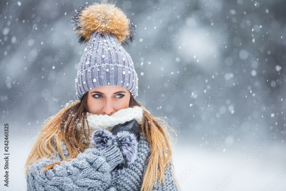 Fototapeta Portrait of young beautiful woman in winter clothes and strong snowing.