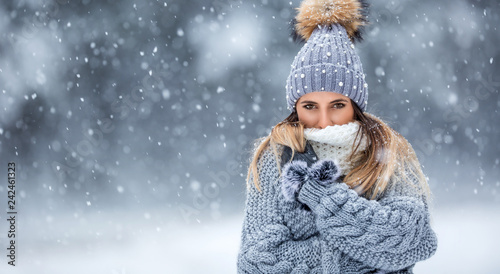 Fototapeta  Portrait of young beautiful woman in winter clothes and strong snowing