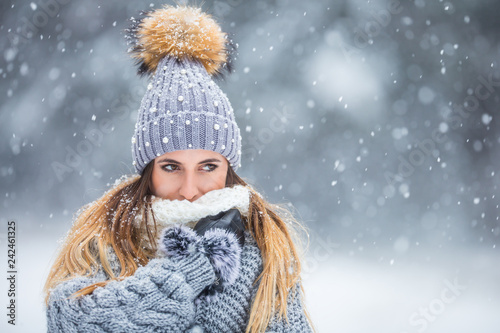 Obraz Portrait of young beautiful woman in winter clothes and strong snowing. - fototapety do salonu