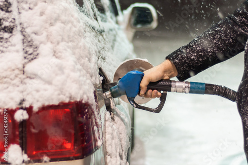 A man in a black coat fills his car at a gas station on a snowy winter evening Fototapeta