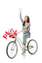 Woman Waving And Riding Vintage Bicycle With Canadian Flags Isolated On White