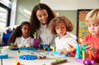 Female teacher sitting at table in play room with three kindergartne children constructing, selective focus