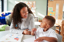 Female Infant School Teacher Working One On One With A Young Schoolboy, Sitting At A Table Smiling At Each Other, Close Up