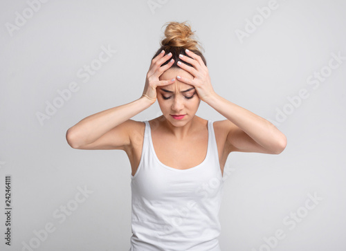 Exhausted woman suffering from unbearable headache over background Wallpaper Mural