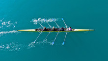 Aerial Drone Bird's Eye Top Down View Of Sport Canoe Operated By Team Of Young Men In Open Ocean Emerald Sea