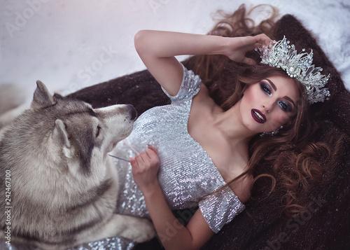 Portret kobiety w srebrnej sukience i koronie jak królowa śniegu, zima w lesie z psem Husky leży na śniegu w futrze ... Czarodziejska księżniczka i wilk zimą.