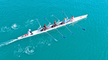 Aerial Drone Bird's Eye Top View Of Sport Canoe Operated By Team Of Young Women In Emerald Clear Sea
