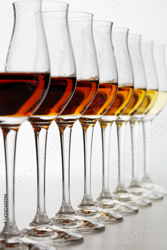 Carta da parati Row of cognac glasses with different stages of aging