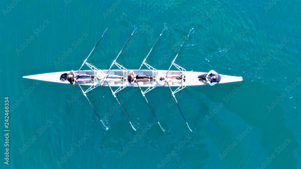 Fototapeta Aerial drone top down view of sport canoe operated by team of young women in emerald clear sea