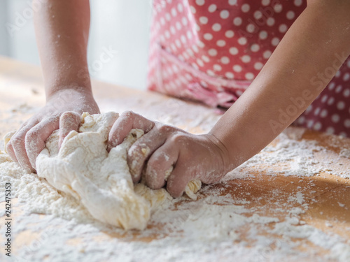 Fotografie, Obraz  Kid hands preparing dough for pizza or bread, lifestyle concept, motion blur
