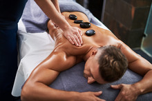 Professional Masseur Massaging Client Body While He Lying On Massage Table