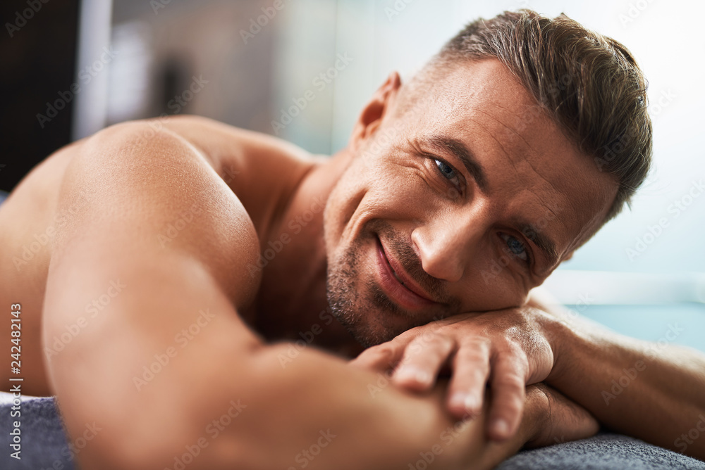 Fototapeta Handsome young man lying on bed and expressing positive emotions