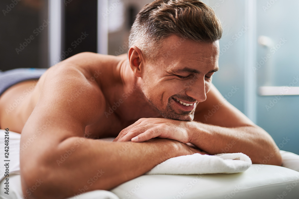 Fototapeta Handsome young man with closed eyes lying on massage table