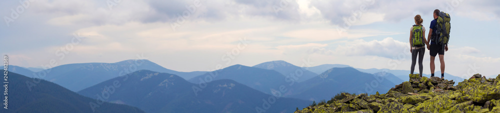 Fototapety, obrazy: Back view of young tourist couple with backpacks, athletic man and slim girl stand holding hands on rocky mountain top enjoying mountain panorama. Tourism, traveling and healthy lifestyle concept.