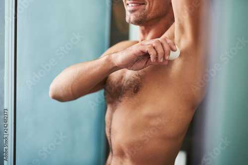 Photo Young man with perfect body applying antiperspirant on armpit