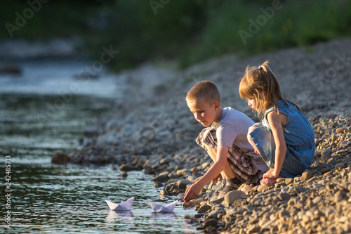 Vászonkép Two cute blond children, boy and girl on river bank sending in water white paper boats on bright summer blurred blue background